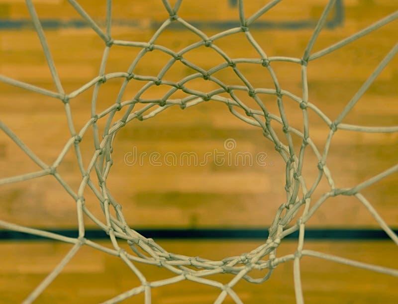 Άποψη μέσω της στεφάνης καλαθοσφαίρισης Να ανατρέξει στο πάτωμα μέσω άσπρου καθαρού από στοκ εικόνες