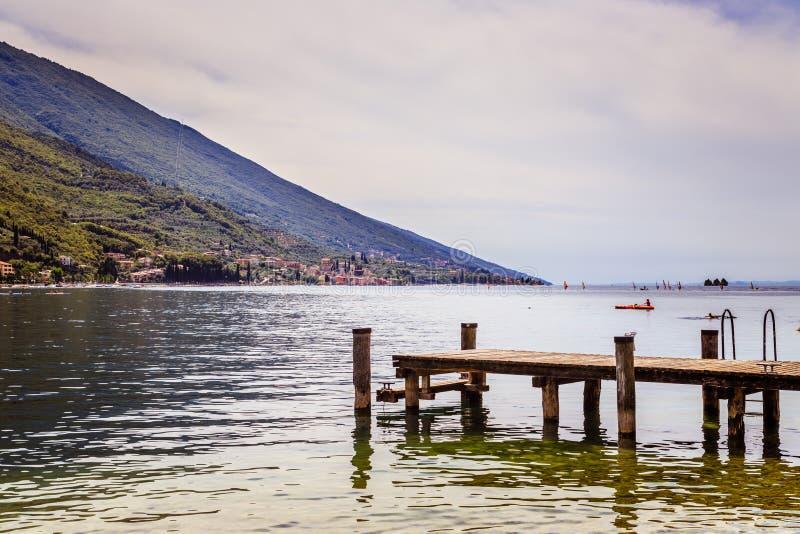 Άποψη με την ξύλινη αποβάθρα αποβαθρών που επεκτείνεται πέρα από το μπλε νερό και τα βουνά λιμνών στοκ εικόνα