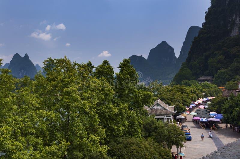 Άποψη μιας οδού markt στην πόλη Yangshuo με τις ψηλές αιχμές ασβεστόλιθων στο υπόβαθρο, στην Κίνα στοκ εικόνες