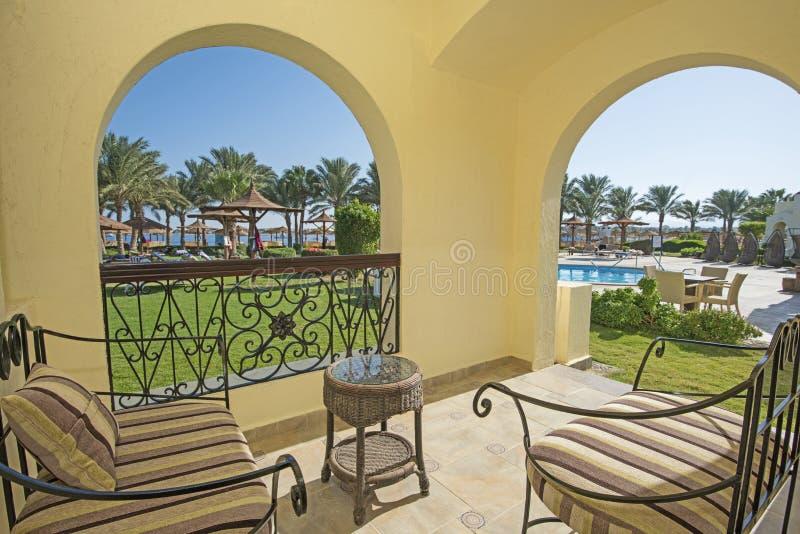 Άποψη μιας τροπικών παραλίας και μιας πισίνας από το δωμάτιο ξενοδοχείου στοκ φωτογραφία