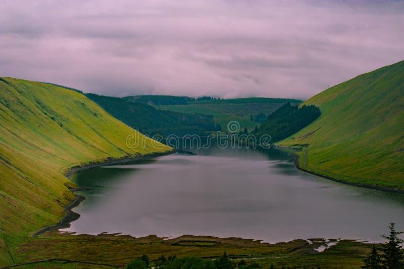 Άποψη μιας beautlful λίμνης Talla στα σκωτσέζικα σύνορα με πράσινο γεια στοκ φωτογραφία
