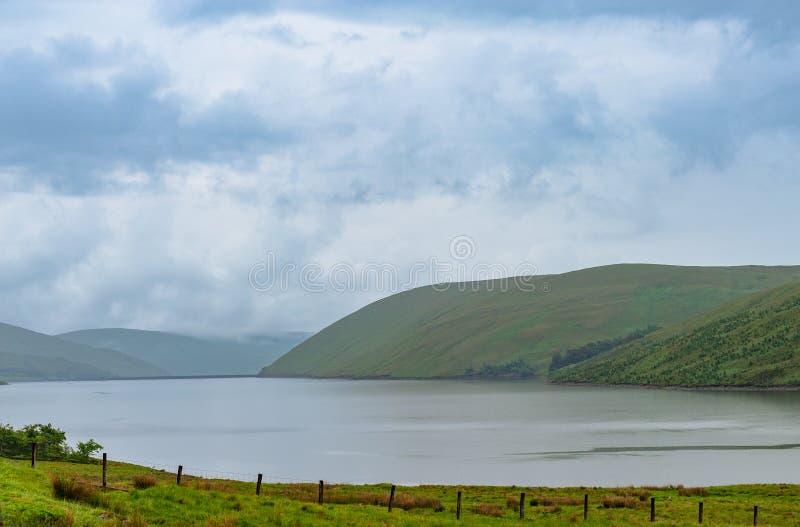 Άποψη μιας beautlful λίμνης Talla στα σκωτσέζικα σύνορα με πράσινο γεια στοκ εικόνες