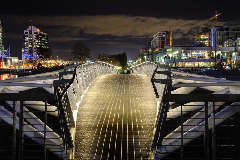 Άποψη νύχτας μιας πόλης με μια για τους πεζούς γέφυρα στο πρώτο πλάνο στοκ εικόνα