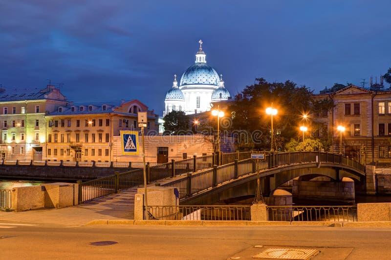 Άποψη νύχτας του καθεδρικού ναού τριάδας πίσω από τα κτήρια και τη γέφυρα Krasnoarmeysky στοκ εικόνες