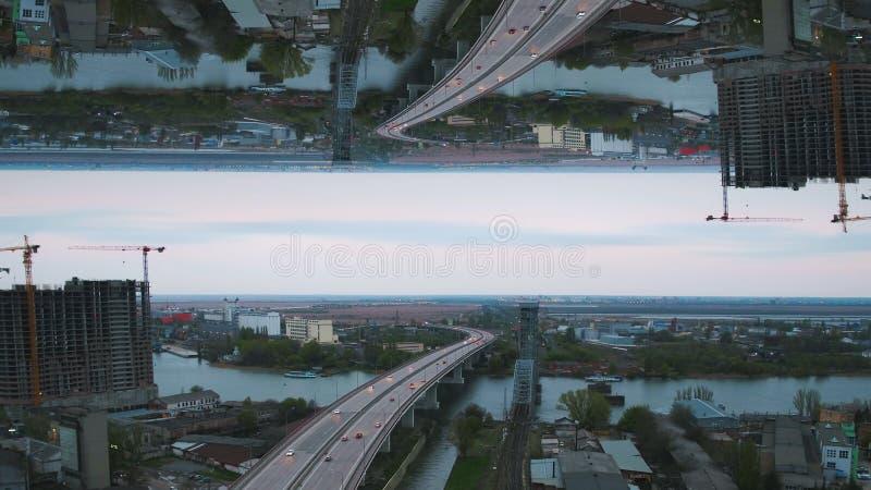 Άποψη ξημερωμάτων της πόλης με τη γέφυρα ποταμών, το ατελές κτήριο και πολλά πράσινα δέντρα, επίδραση οριζόντων καθρεφτών μέσα στοκ φωτογραφία με δικαίωμα ελεύθερης χρήσης
