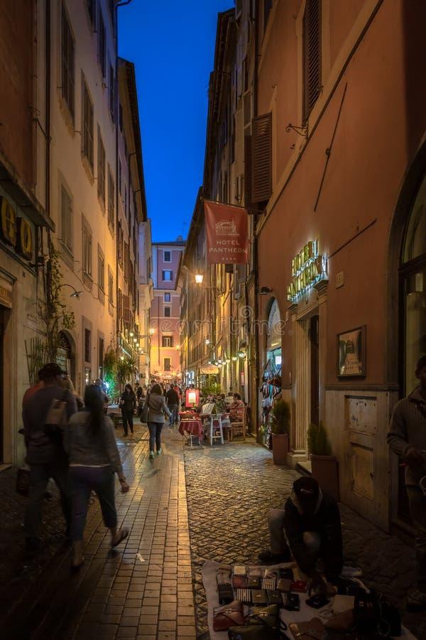 Άποψη οδών νύχτας των ανθρώπων σε μια στενή οδό δίπλα σε έναν γευματίζοντα και ένα ξενοδοχείο στοκ εικόνα με δικαίωμα ελεύθερης χρήσης