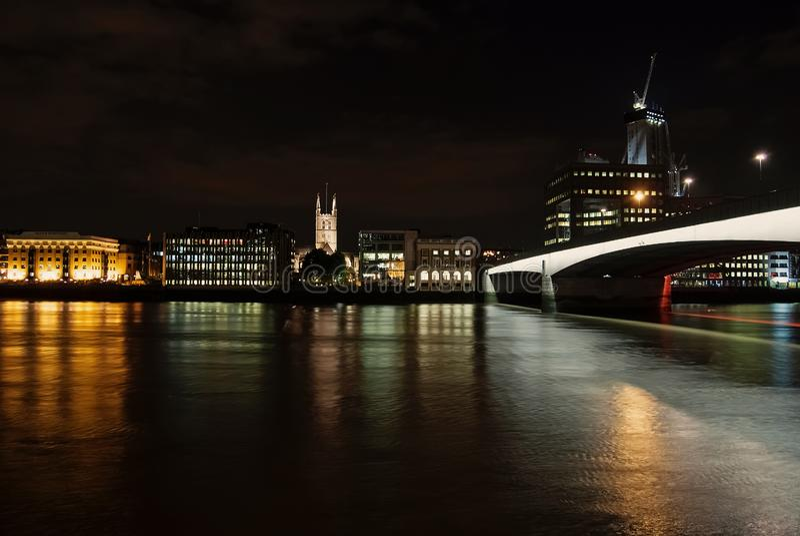 Άποψη οριζόντων από τον ποταμό σκοτεινός ουρανός στο Λονδίνο, Ηνωμένο Βασίλειο Πόλη και γέφυρα με το φωτισμό νύχτας Κτήρια στοκ φωτογραφία