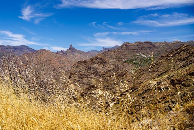 Άποψη πέρα από τα βουνά θλγραν θλθαναρηα με Roque Nublo, Roque Bentayga και το χωριό Carrizal de Tejeda στοκ εικόνες