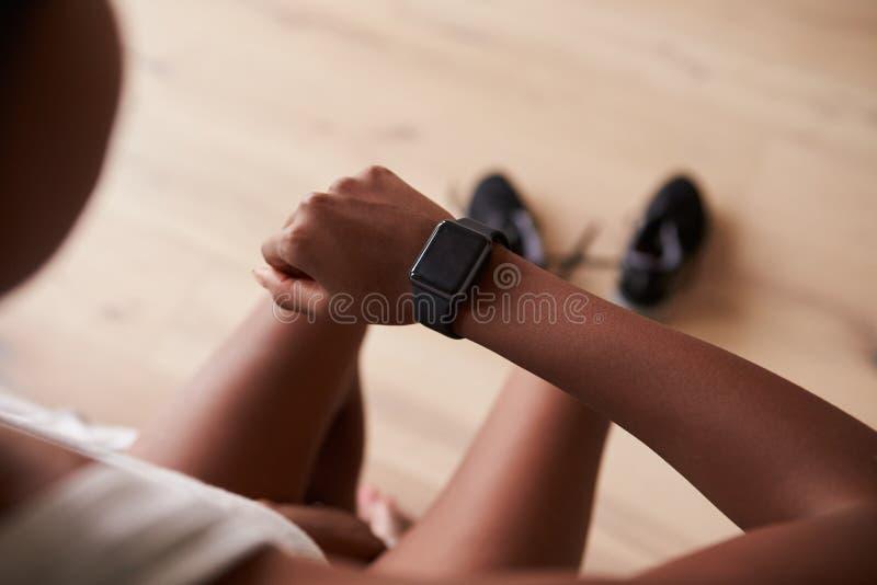 Άποψη πέρα-ώμων της νέας μαύρης γυναίκας που ελέγχει το έξυπνο ρολόι στοκ εικόνες