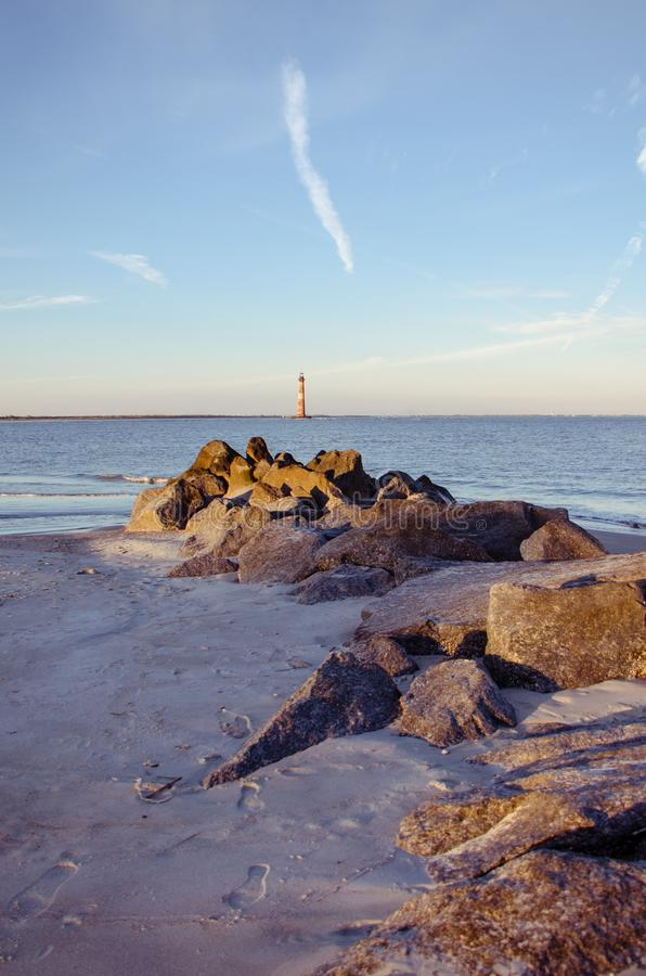 Άποψη πορτρέτου με τους βράχους και την αμμώδη παραλία στο πρώτο πλάνο του φάρου νησιών Morris στοκ εικόνα