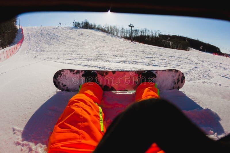 Άποψη που πυροβολείται μιας αρσενικής snowboarder συνεδρίασης στο χιόνι στοκ εικόνες