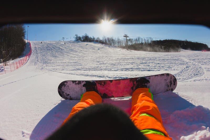 Άποψη που πυροβολείται μιας αρσενικής snowboarder συνεδρίασης στο χιόνι στοκ φωτογραφία με δικαίωμα ελεύθερης χρήσης