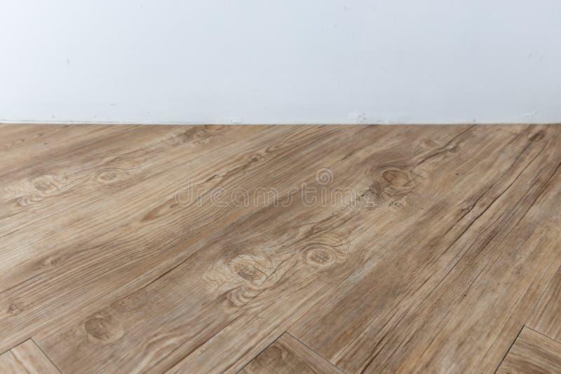Άποψη προοπτικής του κενού εσωτερικού δωματίου με τον άσπρο τοίχο τσιμέντου και το καφετί ξύλινο πάτωμα ψαροκόκκαλων στοκ εικόνα με δικαίωμα ελεύθερης χρήσης