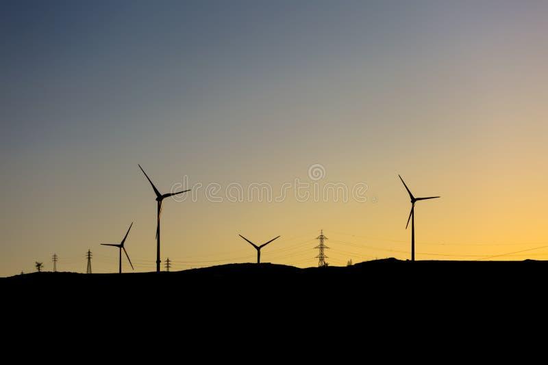 Άποψη σκιαγραφιών ανεμοστρόβιλοι πάνω από τα βουνά, ουρανός ηλιοβασιλέματος στοκ εικόνες με δικαίωμα ελεύθερης χρήσης