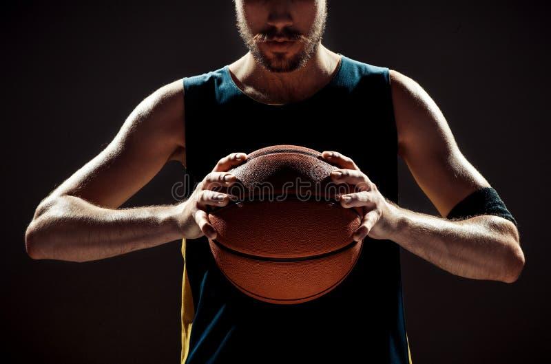 Άποψη σκιαγραφιών μιας σφαίρας καλαθιών εκμετάλλευσης παίχτης μπάσκετ στο μαύρο υπόβαθρο στοκ εικόνα