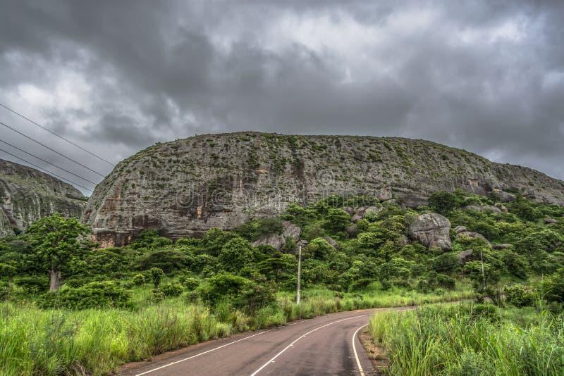 Άποψη στα βουνά Pungo Andongo, Pedras Negras ( μαύρο stones) , τεράστια γεωλογικά στοιχεία, δρόμος και ηλεκτροφόρα καλώδι στοκ φωτογραφία
