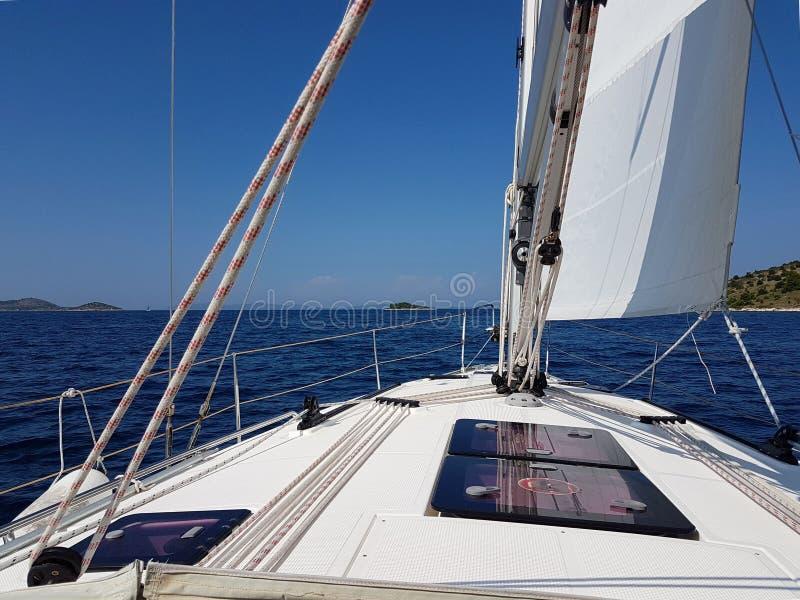 Άποψη στην απόσταση από το πιλοτήριο ενός γιοτ που πλέει μετά από τα πράσινα νησιά ενάντια σε έναν μπλε σαφή ουρανό Ενεργά υπόλοι στοκ εικόνα με δικαίωμα ελεύθερης χρήσης