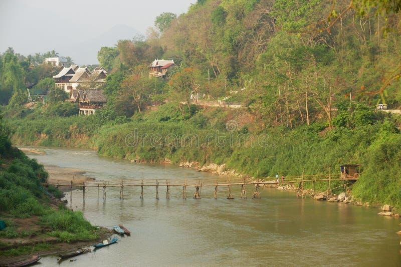 Άποψη στη κατοικήσιμη περιοχή της πόλης πέρα από τον ποταμό με μια γέφυρα σε Luang Prabang, Λάος στοκ εικόνες