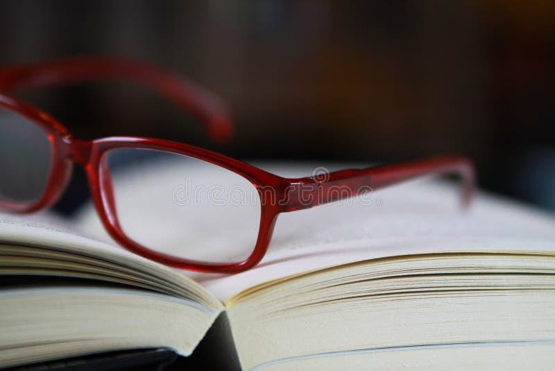 Άποψη στις σελίδες του ανοικτού βιβλίου με τα κόκκινα γυαλιά ανάγνωσης στοκ εικόνες
