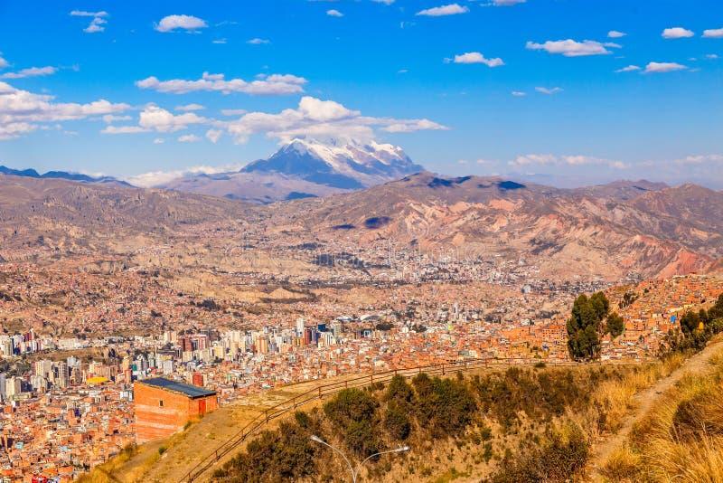 άποψη στο χιόνι ΚΑΠ της αιχμής Illimani και του συνόλου κοιλάδων των σπιτιών διαβίωσης, EL Alto, πόλη Λα Παζ, Βολιβία στοκ φωτογραφίες