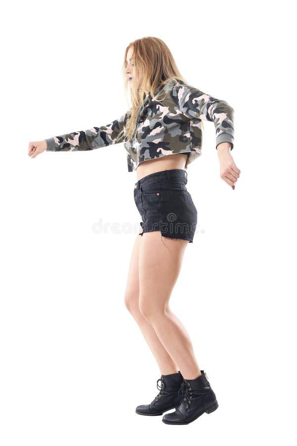 Άποψη σχεδιαγράμματος του προκλητικού ξανθού καυκάσιου χορού γυναικών στο στρατιωτικό σακάκι κάλυψης με τη σφιγγμένη πυγμή στοκ εικόνες με δικαίωμα ελεύθερης χρήσης
