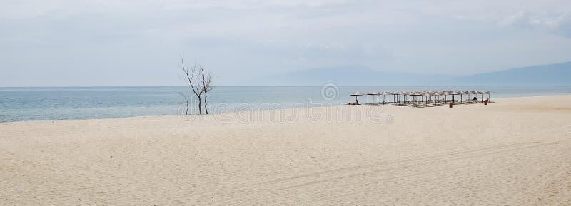 Άποψη σχετικά με την ατελείωτη αμμώδη παραλία, ομπρέλες, sunbeds στην Ελλάδα στοκ φωτογραφίες
