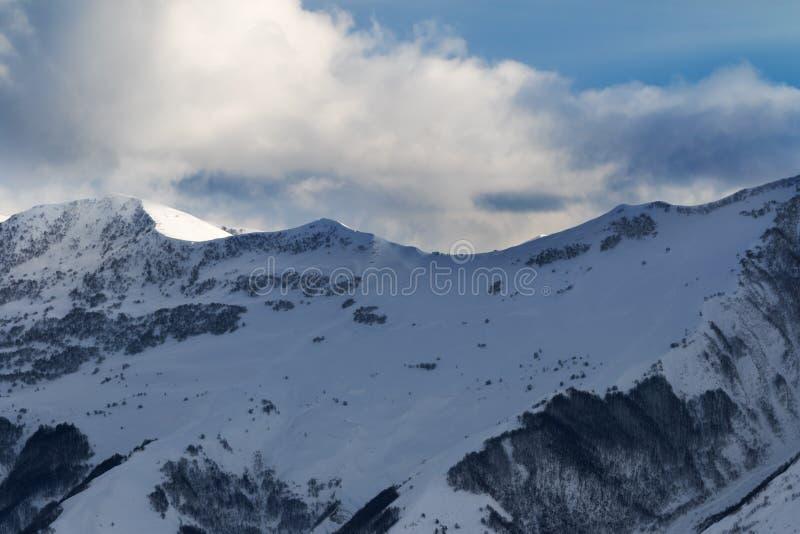 Άποψη σχετικά με τη off-piste κλίση με το δάσος και τον ουρανό φωτός του ήλιου με τα σύννεφα στοκ εικόνες