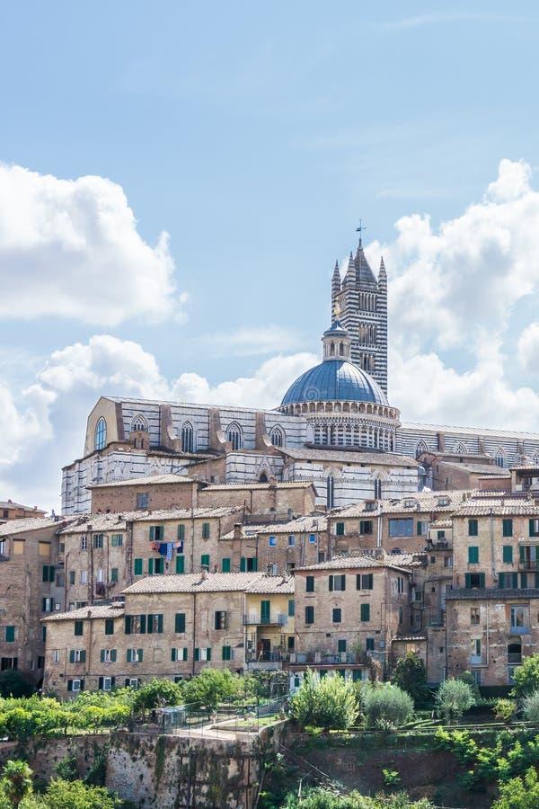 Άποψη σχετικά με το διάσημο καθεδρικό ναό στην πόλη της Σιένα πίσω από άλλα ιστορικά κτήρια στοκ εικόνες με δικαίωμα ελεύθερης χρήσης