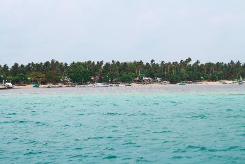 Άποψη της άσπρης παραλίας άμμου από απόσταση με τα παραταγμένα πράσινα & τα δέντρα στο υπόβαθρο στοκ εικόνα