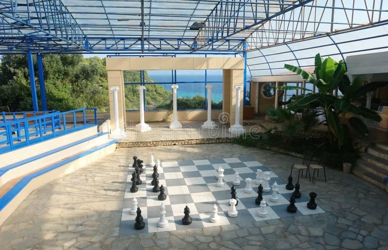 Άποψη της αίθουσας με τα μεγάλα κομμάτια σκακιού και η άποψη της μπλε θάλασσας σε ένα ελληνικό ξενοδοχείο στοκ φωτογραφία
