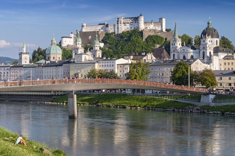 Άποψη της γέφυρας Makartsteg πέρα από τον ποταμό Salzach και Hohensalzburg Castle επάνω από την παλαιά πόλη του Σάλτζμπουργκ, Αυσ στοκ εικόνα