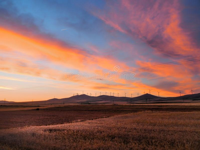 Άποψη της γεωργικής περιοχής και των ανεμολογίων στο βουνό στο ηλιοβασίλεμα στοκ εικόνες