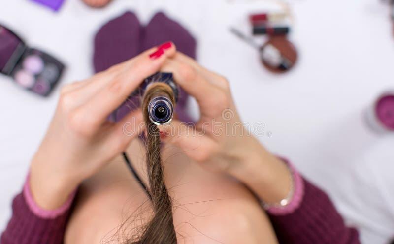 Άποψη της γυναίκας που χρησιμοποιεί τον κατσαρώνοντας σίδηρο στοκ φωτογραφία με δικαίωμα ελεύθερης χρήσης