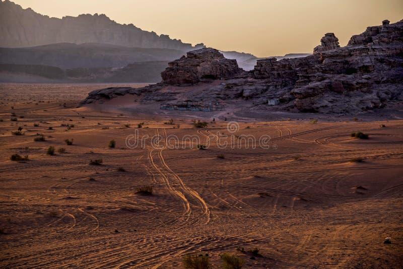 Άποψη της ερήμου wadi-ρουμιού σε Jordanié, με τα ακανόνιστα υψηλά βουνά του και την κόκκινος-χρυσή άμμο στο ηλιοβασίλεμα στοκ φωτογραφία