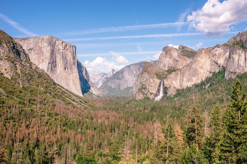 Άποψη της κοιλάδας Yosemite από το σημείο άποψης σηράγγων - άποψη στο νυφικό πέπλο πέφτουν, η EL Capitan και ο μισός θόλος - εθνι στοκ εικόνα