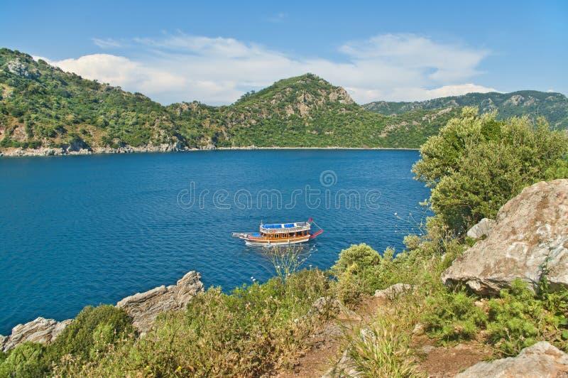 Άποψη της μικρής βάρκας τουριστών στον κόλπο από τον απότομο βράχο στοκ εικόνα με δικαίωμα ελεύθερης χρήσης