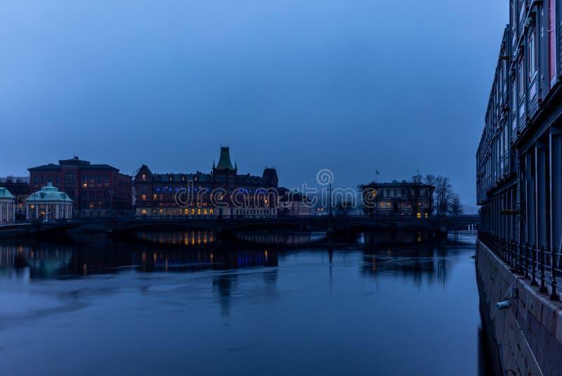 Άποψη της οικοδόμησης του Norstedts Foerlag στη Στοκχόλμη και της γέφυρας Vasabron που απεικονίζει στη θάλασσα το βράδυ στοκ εικόνες