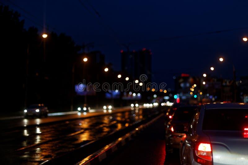 Άποψη της πόλης νύχτας, αυτοκίνητα στην οδό, θολωμένο φως στοκ εικόνες