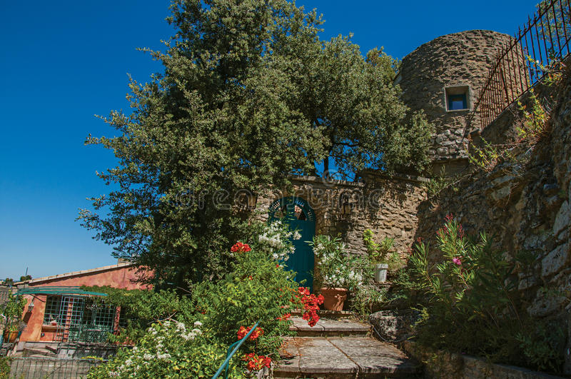 Άποψη της σκάλας και της πύλης με τα λουλούδια και του ηλιόλουστου μπλε ουρανού στο υπόβαθρο, στο χωριό Ménerbes στοκ φωτογραφίες