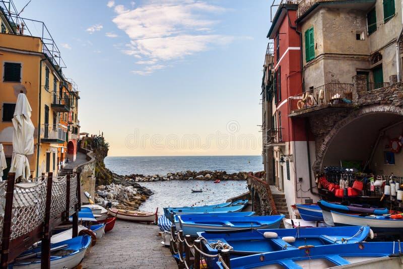 Άποψη της στενής οδού με τις βάρκες και της θάλασσας σε Riomaggiore, Cinque Terre Ιταλία στοκ φωτογραφίες