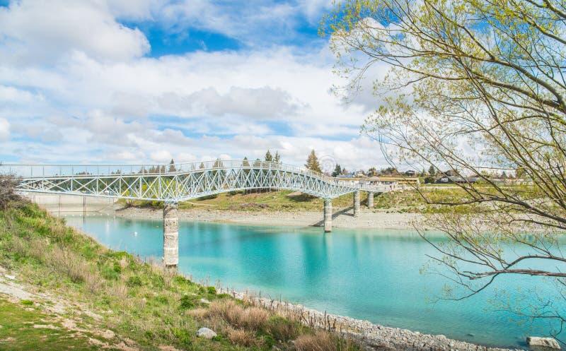 Άποψη τοπίου της γέφυρας για πεζούς Tekapo λιμνών πέρα από το ζαλίζοντας νερό της λίμνης Tekapo στο νότιο νησί, Νέα Ζηλανδία στοκ εικόνες