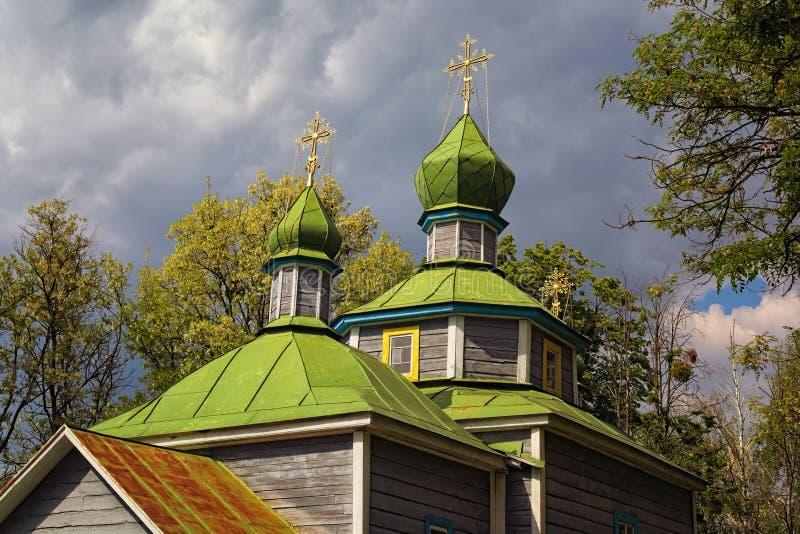 Άποψη τοπίων της αρχαίας ξύλινης εκκλησίας cossack ενάντια στο νεφελώδη ουρανό Λεπτά πριν από τη καταιγίδα άνοιξη στοκ εικόνα