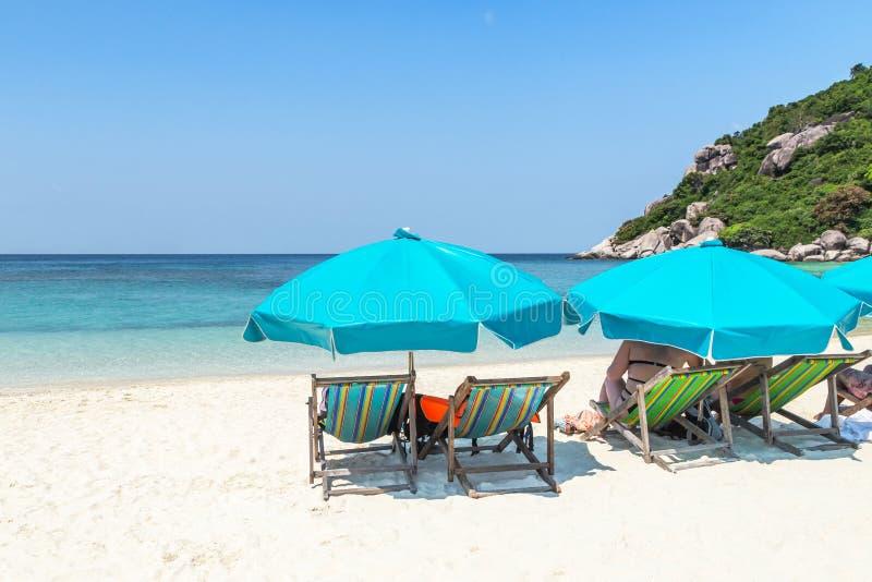 Άποψη τοπίων των μπλε ομπρελών με τις ξύλινες καρέκλες παραλιών στην τροπική αμμώδη παραλία στην ηλιόλουστη ημέρα στοκ φωτογραφία με δικαίωμα ελεύθερης χρήσης