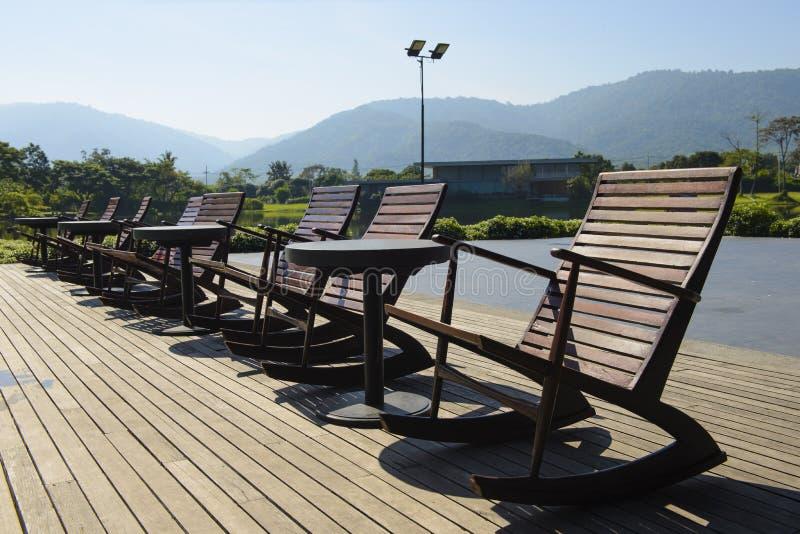 Άποψη τοπίων των ξύλινων καρεκλών στο poolside στοκ φωτογραφία με δικαίωμα ελεύθερης χρήσης