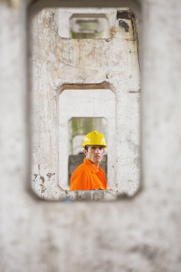 Άποψη του αρσενικού αρχιτέκτονα μέσω των στυλοβατών στο εργοτάξιο οικοδομής στοκ φωτογραφία