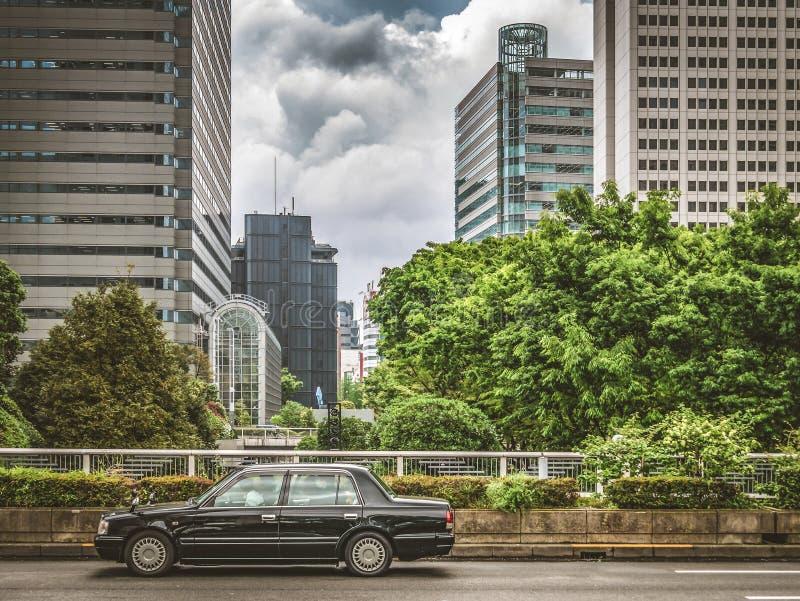 Άποψη του αυτοκινήτου ταξί μπροστά από τα skyscrappers στην οδό με τα ζωηρόχρωμα δέντρα και τον ουρανό στο υπόβαθρο στοκ εικόνες με δικαίωμα ελεύθερης χρήσης