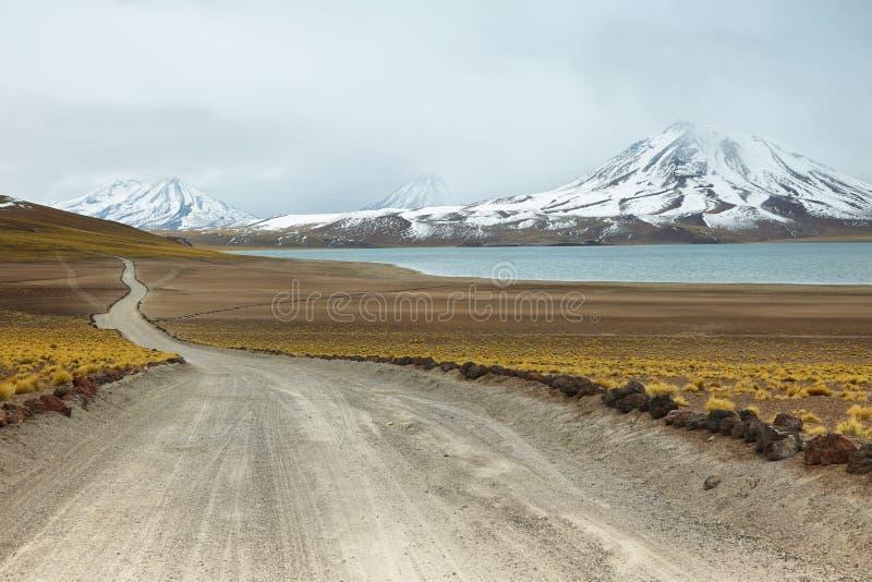 Άποψη του βρώμικου δρόμου και της λιμνοθάλασσας Miscanti στο πέρασμα Sico στοκ εικόνες