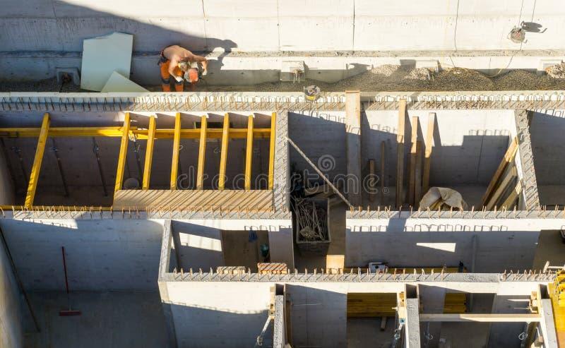 Άποψη του εργοτάξιου οικοδομής και ανύπαντρο εργαζόμενος άνωθεν στοκ φωτογραφία