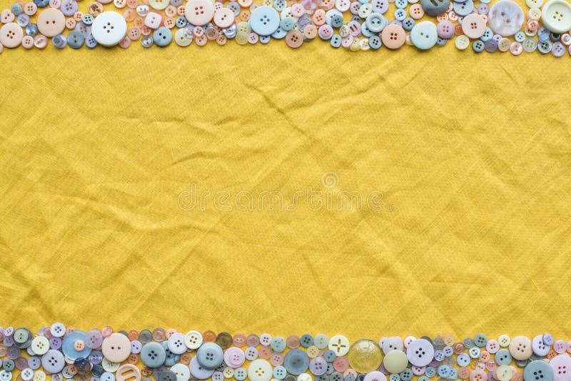 Άποψη του ζωηρόχρωμου πλαισίου κουμπιών στο κίτρινο υπόβαθρο υφασμάτων με το διάστημα αντιγράφων στοκ εικόνα