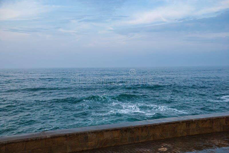 Άποψη του θαλάσσιου περιπάτου με τον τοίχο, την μπλε θάλασσα και το νεφελώδη ουρανό στοκ εικόνες